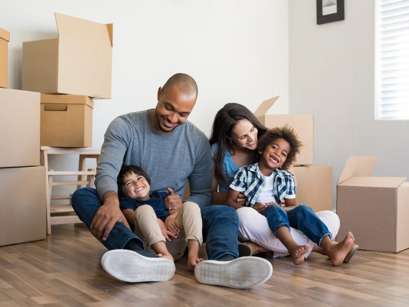 Happy family with two children having fun at new home. Young multiethnic parents with two sons in their new house with cardboard boxes. Smiling little boys sitting on floor with mother and dad.